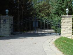 Custom Gate design with Camera, keypad and stone pillars using a black steel gate
