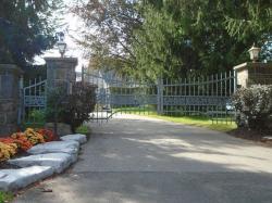 Custom design gray gate with control box located near roadway